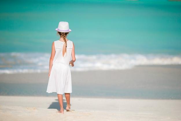 楽しんでビーチでドレスの美しい少女。