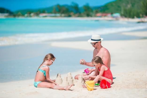 熱帯の白いビーチで砂の城を作る家族