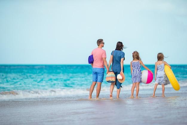白いビーチで幸せな美しい家族