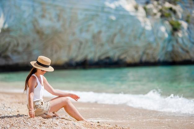 海を見て夏休みを楽しんでいるビーチに敷設する女性