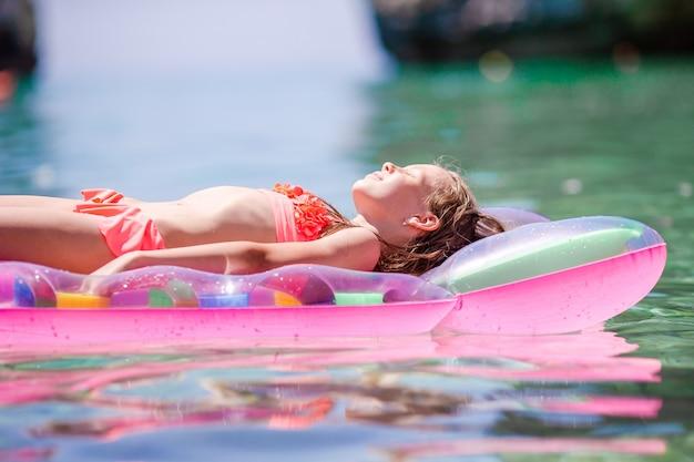 海で膨脹可能なエアマットレスの上のかわいい女の子