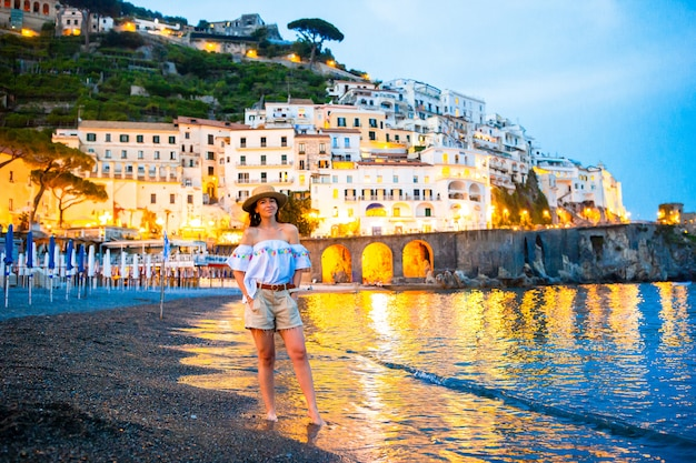 Женщина на закате в городе амальфи в италии