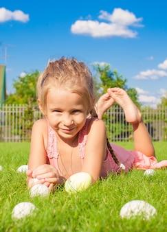 Портрет маленькая счастливая девушка играет с белыми пасхальными яйцами на зеленой траве