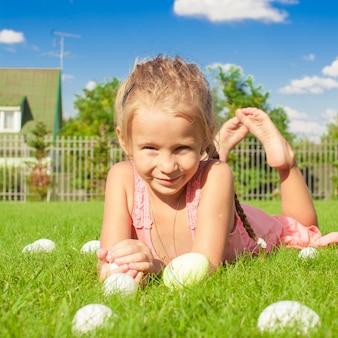 Портрет маленькая милая девушка играет с белыми пасхальными яйцами на зеленой траве