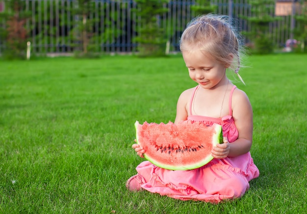 緑の芝生の上の手でスイカの大きな部分を持つ少女