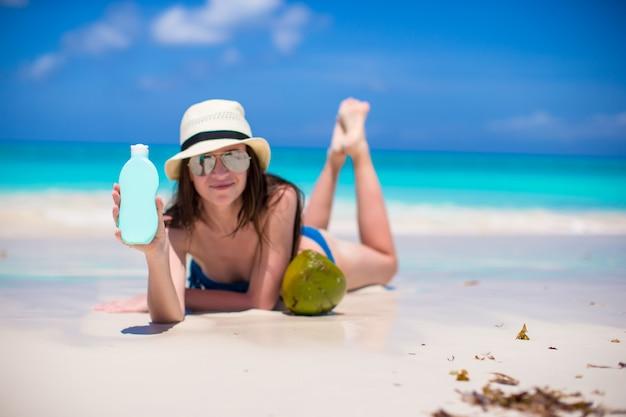 Красивая молодая женщина, держащая крем лежал на тропическом пляже