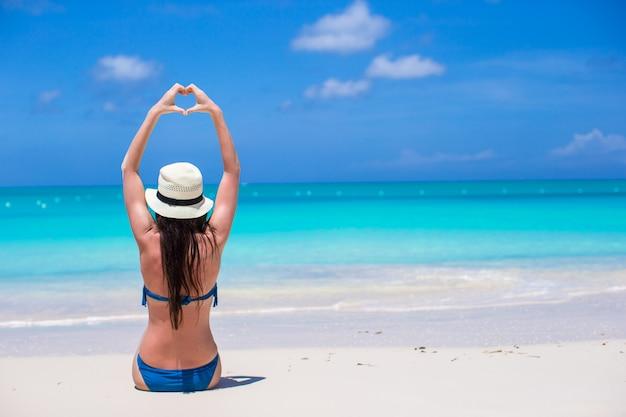 ビーチで手でハートを作る魅力的な若い女性