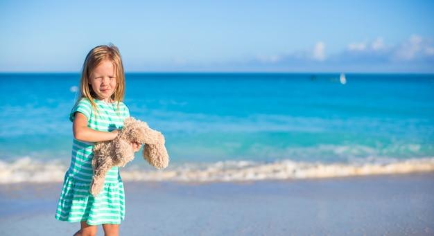 熱帯のビーチでの休暇に彼女のウサギのおもちゃでのかわいい女の子