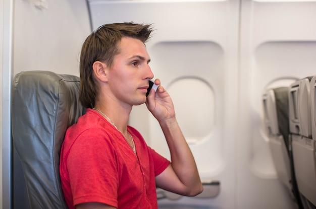 Молодой человек разговаривает по телефону внутри самолета