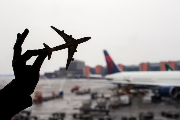 空港の背景に小さな飛行機モデルのシルエット
