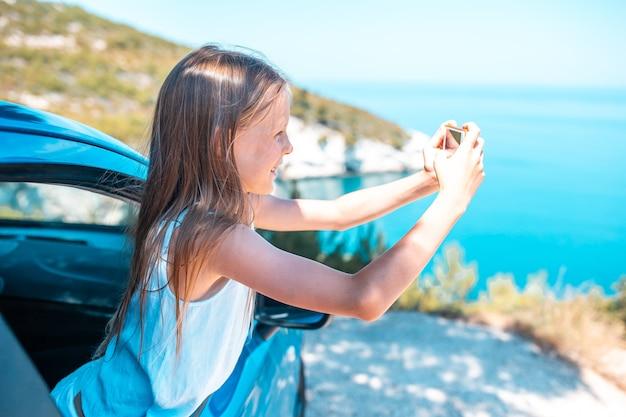 休暇中の少女は車で旅行します。