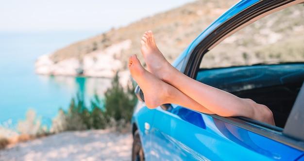 車の窓から示す小さな女の子の足のクローズアップ