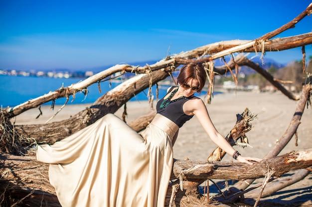 ビーチでポーズをとって長く美しいドレスの魅力的な若い女性