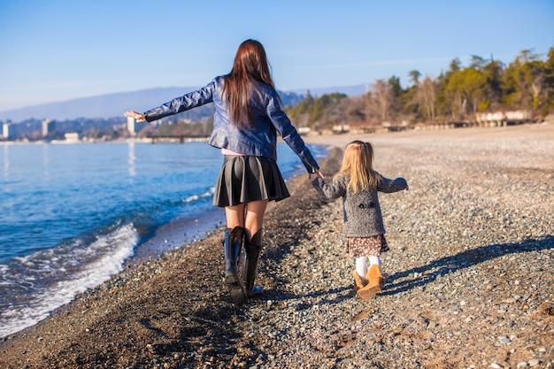 小さな女の子と彼女の母親は冬の晴れた日にビーチを歩いて