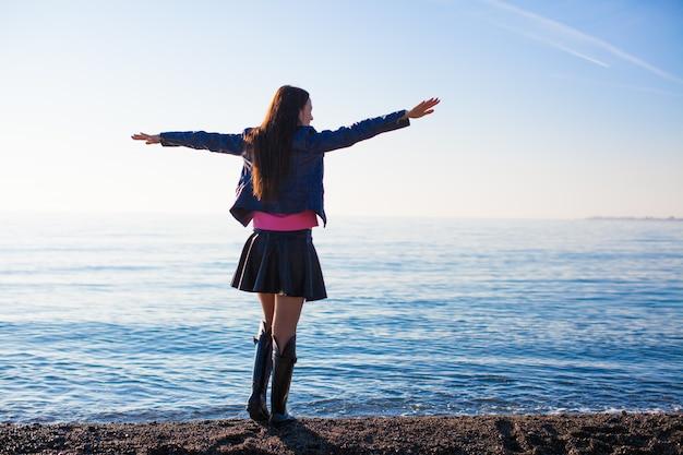 休日を楽しんでいる若い美しい女性がビーチで手を広げて