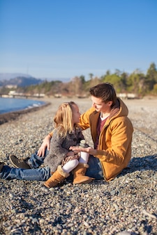 若い父親と晴れた冬の日にビーチで小さな女の子