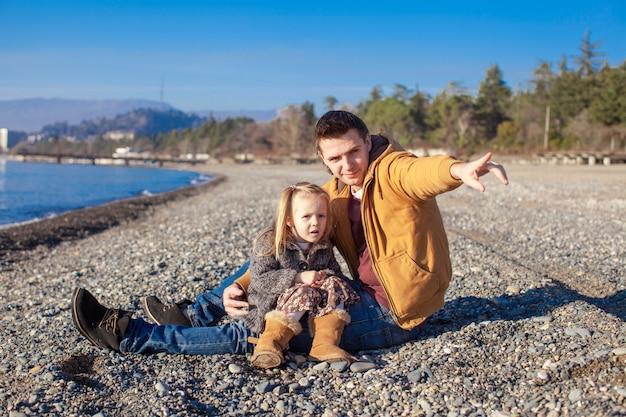 晴れた冬の日にビーチで小さな女の子と若い父