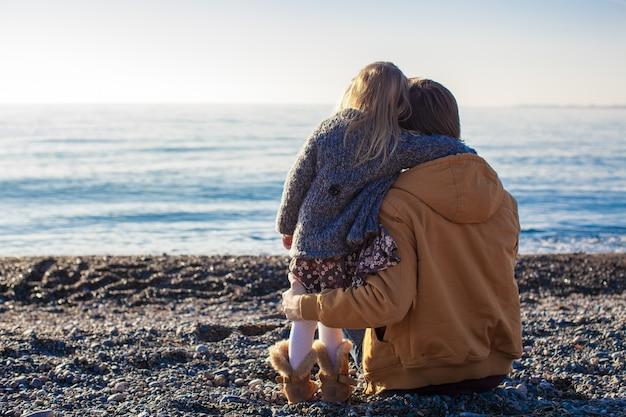 若い父親と晴れた冬の日にビーチで小さな女の子の背面図