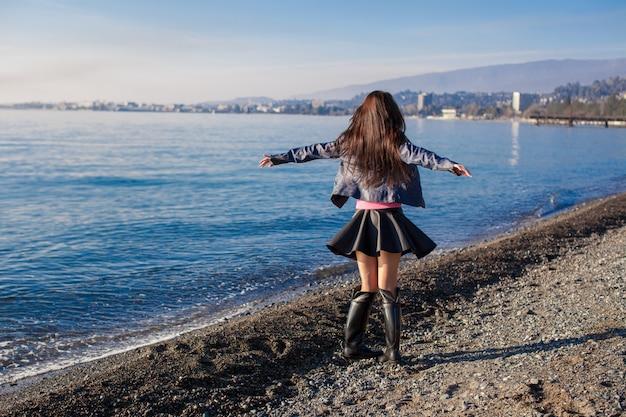 美しい若い女性は一人で冬の晴れた日のビーチでリラックスします。