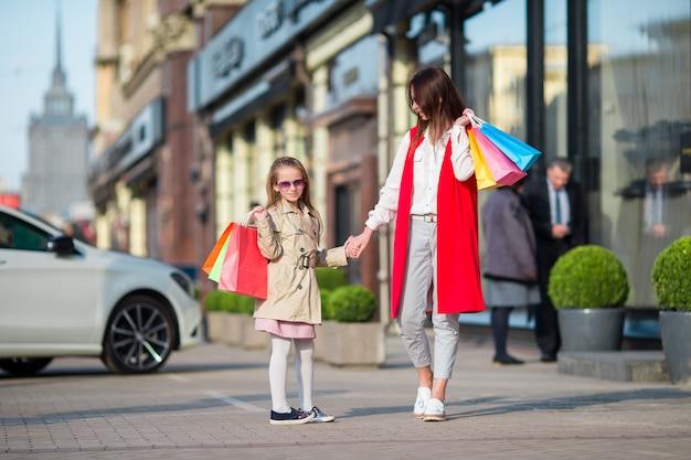 屋外でのショッピングで幸せな家族。母と娘は買い物で買い物をし、屋外の通りを歩いて楽しんでいます。