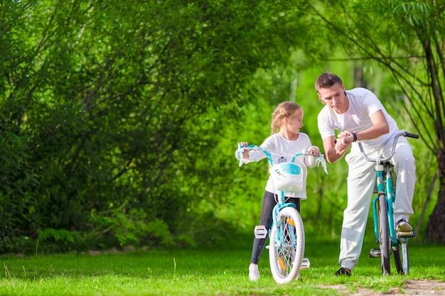 若い父親と夏の暖かい日に自転車に乗る少女。アクティブな若い家族が自転車に乗る