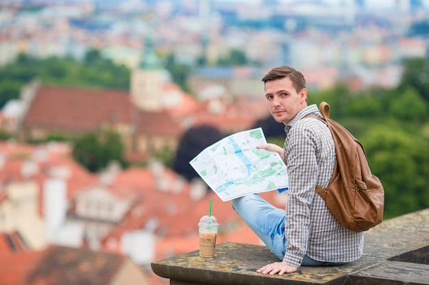 市内地図とバックパックを持つ若者