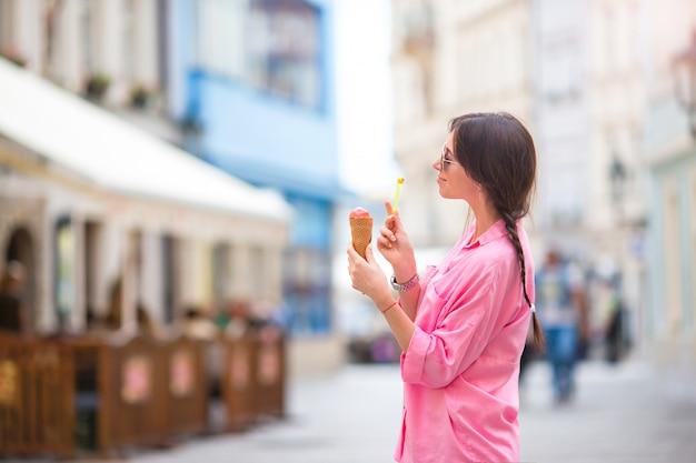 屋外アイスクリームコーンを食べる若い女性モデル。夏のコンセプト-暑い日に甘いアイスクリームを持つ女性
