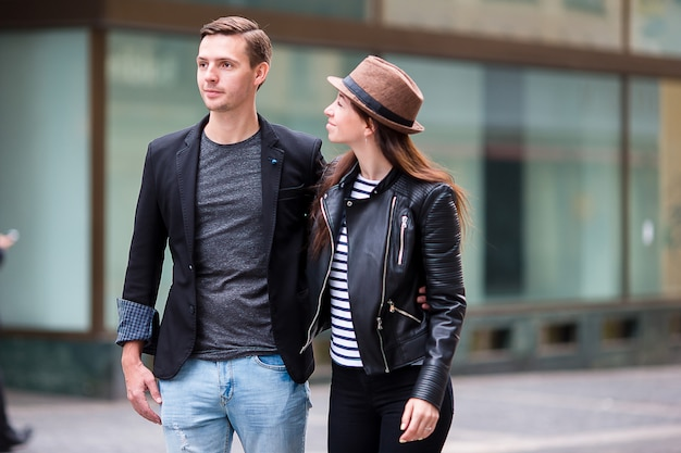 Счастливая пара прогулки в европе. улыбающиеся любители, наслаждающиеся городским пейзажем с известными достопримечательностями.