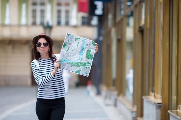 ヨーロッパの市内地図と幸せな若い女。ヨーロッパの休日の間に屋外の地図と旅行のツーリストの女性