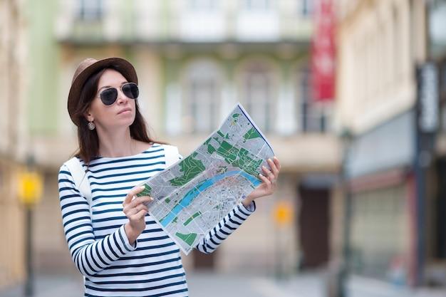Счастливая молодая женщина с картой города в европе. путешествие туристическая женщина с картой в праге на открытом воздухе во время каникул в европе.