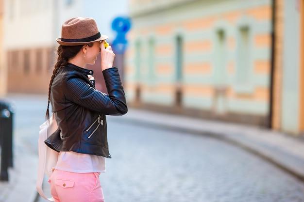 ヨーロッパの観光客がカメラで写真を撮る。チェコ共和国での旅行の女性