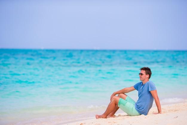 白い砂浜のビーチで音楽を楽しんでいる若い男。夏の熱帯の休暇でリラックスした幸せな観光客。