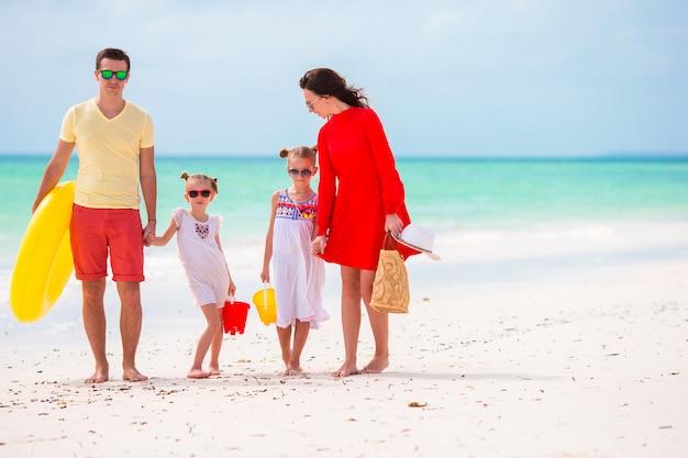 バカンスの若い家族。幸せな父、母と彼らのかわいい子供たちが夏のビーチの休日に楽しんで