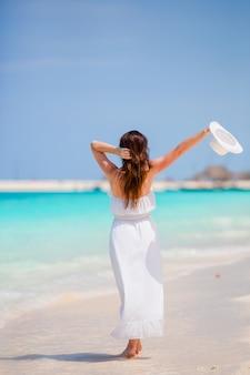 ビーチでの休暇に若くてきれいな女性。幸せな女の子は、海に沿って歩きながらビーチと暖かい天気をお楽しみください