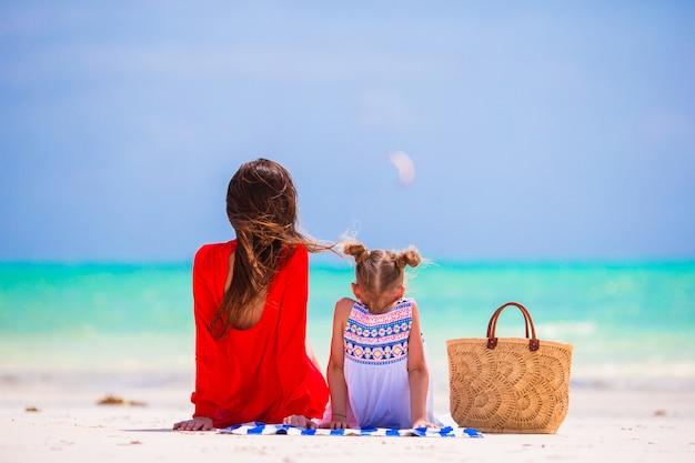 母と娘は熱帯のビーチでの時間を楽しんでいます。夏休みにストローバッグで幸せな家族