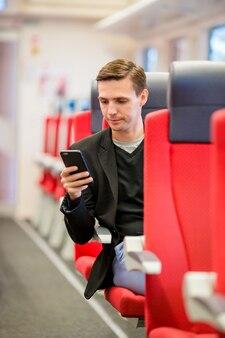 電車で旅行する若い幸せな男。急行列車で旅行中に携帯電話でメッセージを書く観光客