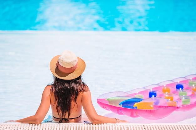 スイミングプールでリラックスした美しい若い女性。
