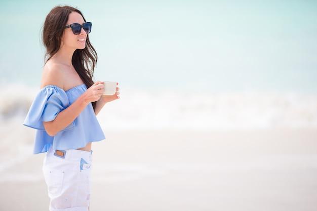 ビーチの景色を楽しみながらホットコーヒーを持つ若い女。
