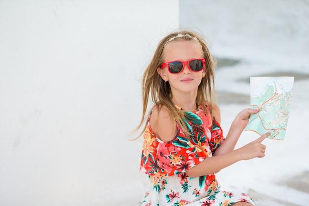 Маленькая девочка с картой острова на открытом воздухе на старых улицах миконоса. ребенок на улице типичной греческой традиционной деревни с белыми стенами и красочными дверями на острове миконос, в греции