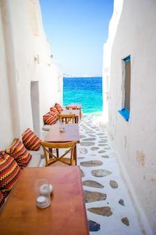 ミコノス島の典型的なギリシャバーの枕とベンチ、キクラデス諸島の素晴らしい海の景色