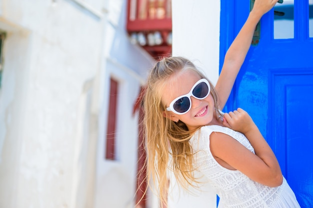 Очаровательны девушка в белом платье на открытом воздухе на старых улицах миконоса. ребенок на улице типичной греческой традиционной деревни с белыми стенами и красочными дверями на острове миконос, в греции