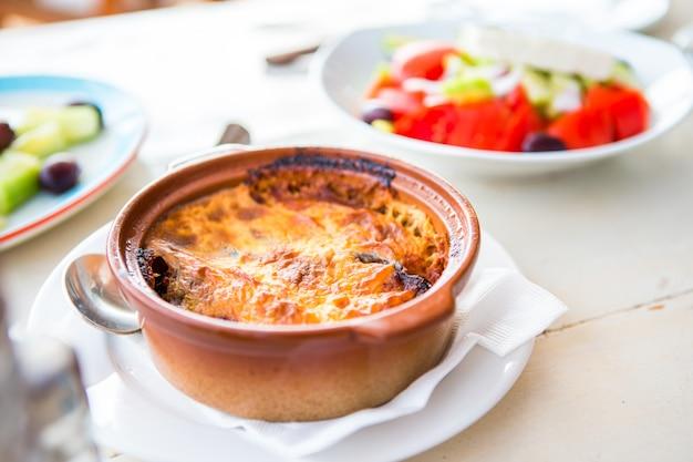 海と港の美しい景色を望む屋外レストランで、ムサカとおいしい新鮮なギリシャ風サラダを添えた伝統的なランチをランチに提供