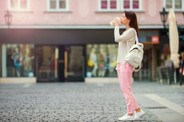 ヨーロッパの都市で幸せな若い都市の女性。ヨーロッパのさびれた通りに沿って歩く白人観光客。