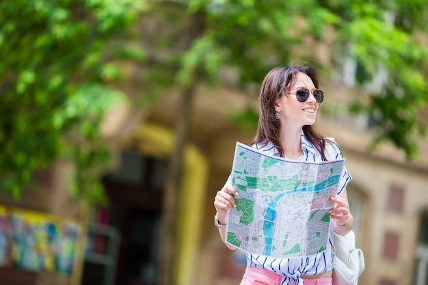 市内地図屋外で幸せな若い女性観光客。ヨーロッパでの休暇中に外の地図で白人の女の子を旅行します。