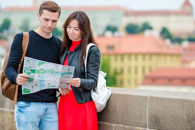 Молодые туристические пары путешествуя на праздниках в европе усмехаясь счастливых. кавказская семья с картой города в поисках достопримечательностей