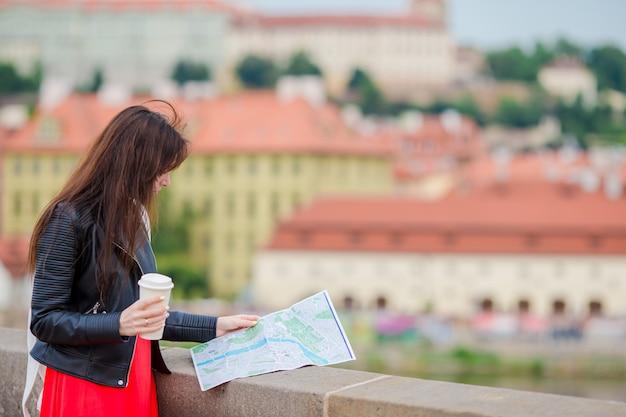 ヨーロッパの市内地図と幸せな若い女。ヨーロッパでの休暇中に屋外の地図で観光女性を旅行します。