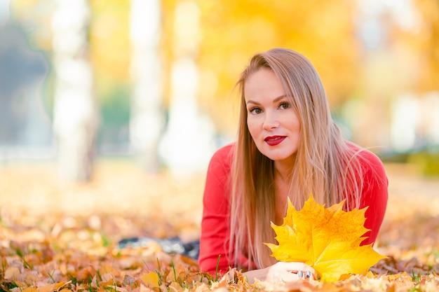 秋の紅葉の下で秋の公園でコーヒーを飲みながら美しい女性
