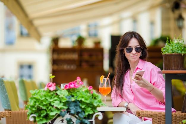 Портрет молодой красивой женщины, сидя в кафе открытый пить вкусный коктейль. счастливый турист наслаждается европейским отдыхом в ресторане под открытым небом