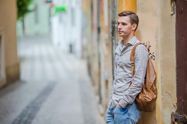 ヨーロッパのさびれた通りに沿って歩く白人観光客。ヨーロッパの都市を探索する休暇の都市少年