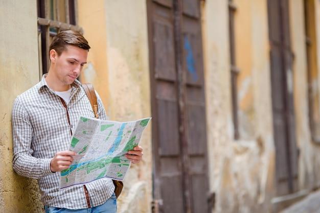 市内地図とヨーロッパ通りのバックパックを持つ男観光客。アトラクションを求めてヨーロッパの都市の地図で見ている白人の少年。